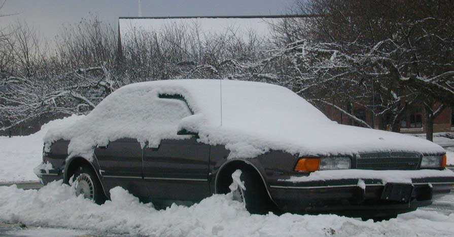 A snowed under sedan with a cold battery.