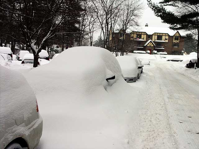 Car parked on the side of the road, buried in snow.