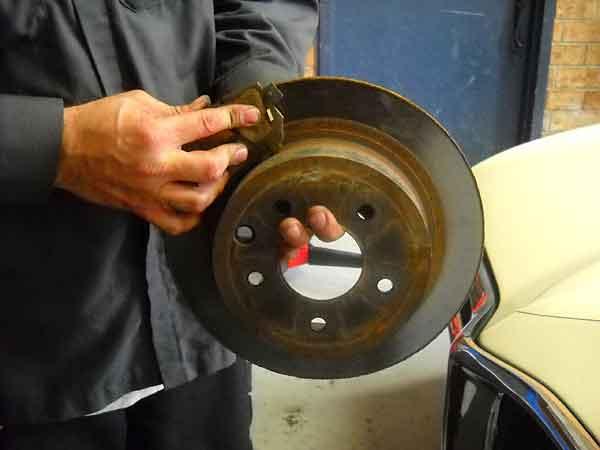An auto mechanic shows how brake pads work.