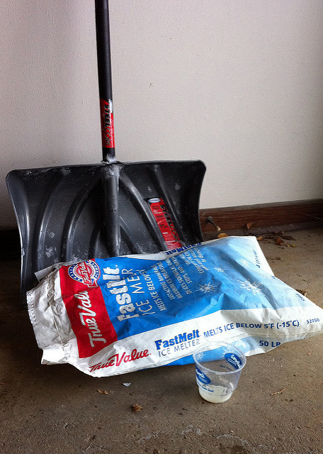 a snow shovel and ice melt leaning against a garage wall