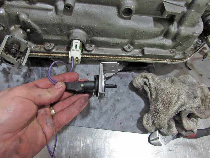The plug connects to the transmission case and the vacuum switch mounts under the hood to manifold vacuum.