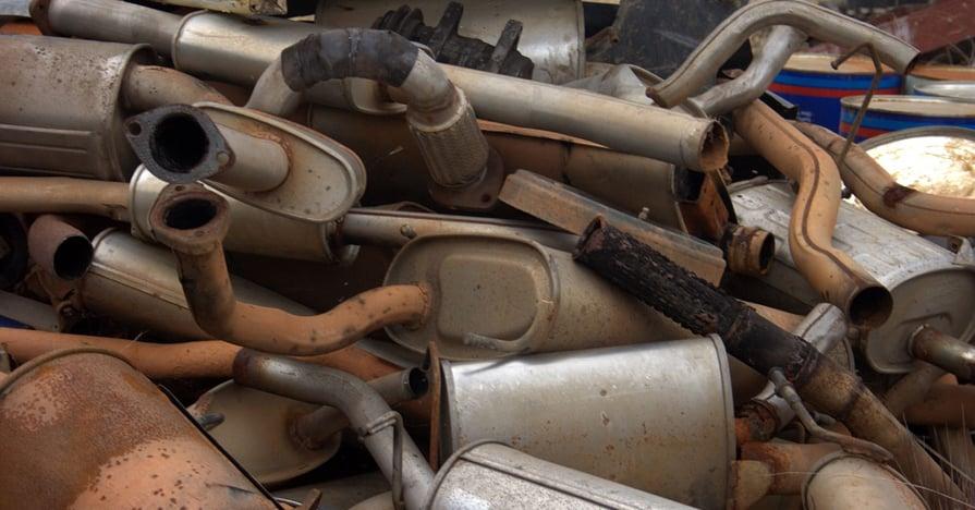 rusty mufflers in a pile