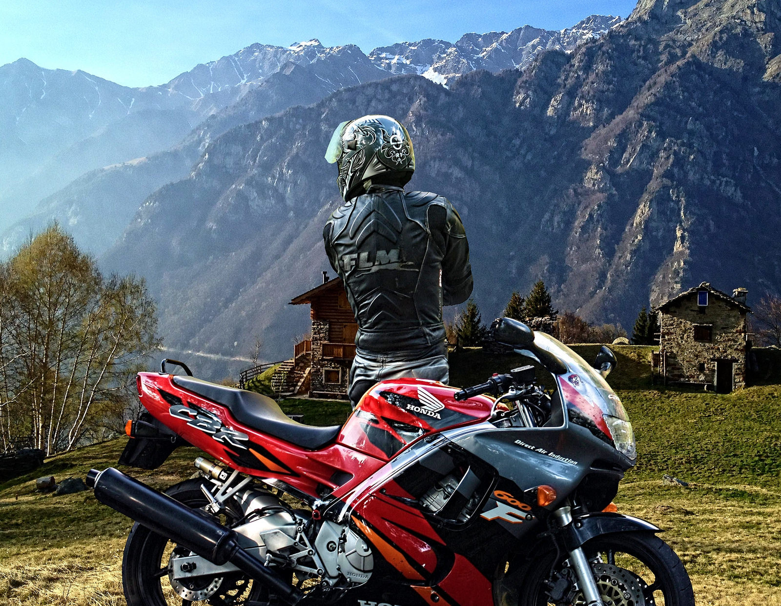 a motorcyclists wearing a helmet after getting off his bike in an idyllic landscape