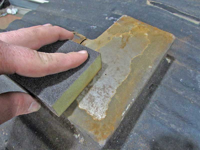 Using a sanding block, the paint and rust scale was removed from the tank.