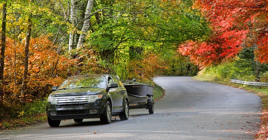 A car towing a boat down an autumnal road, ready for end-of-summer car care.