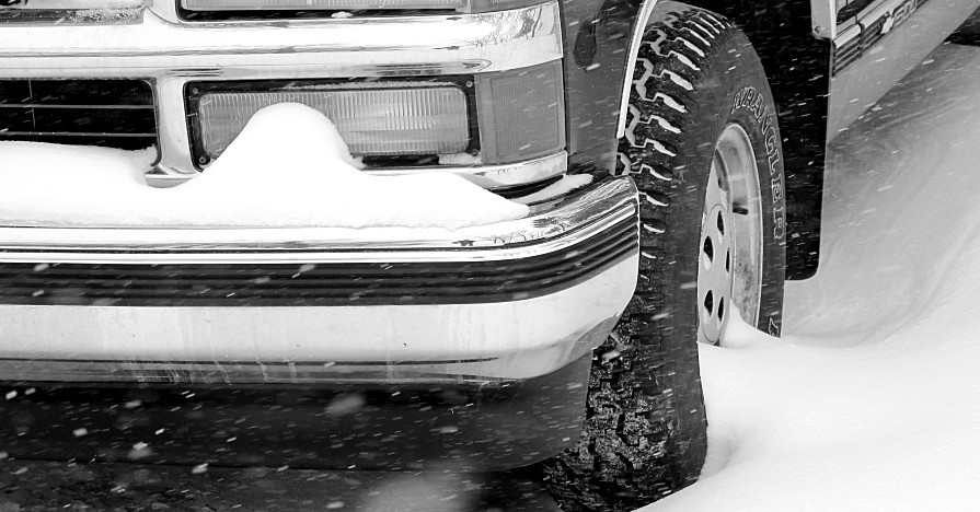 The front wheel and grille of a pickup truck driving during a snow storm.