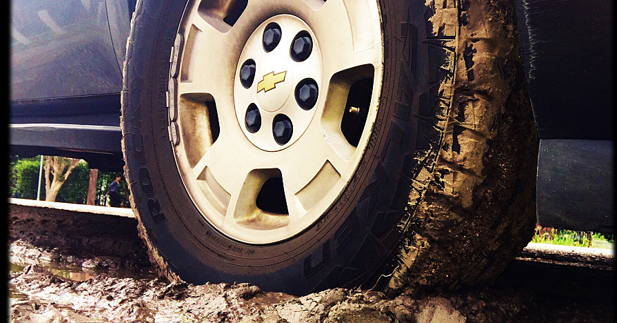A tire on a car stuck in mud.