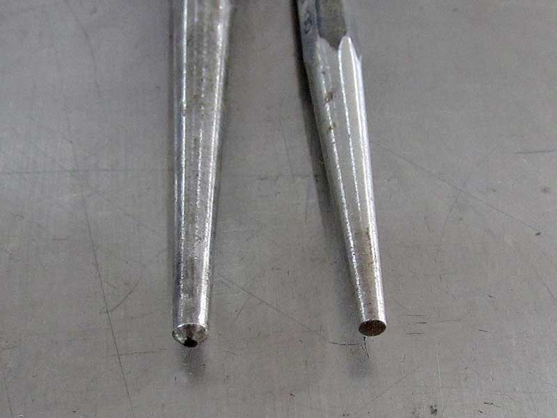 A center punch (left) has a sharp tip, unlike a taper punch (right) which is flat.
