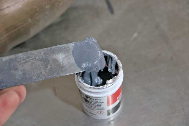 """We scooped up a bit of ExtremeHeat on a metal body filler <a href=""""https://www.napaonline.com/en/p/SER772000?cid=social_blog_112017_JB_Weld_ExtremeHeat"""" target=""""_blank"""" rel=""""noopener"""">spreader</a>. You can put what you don't use back into the jar."""