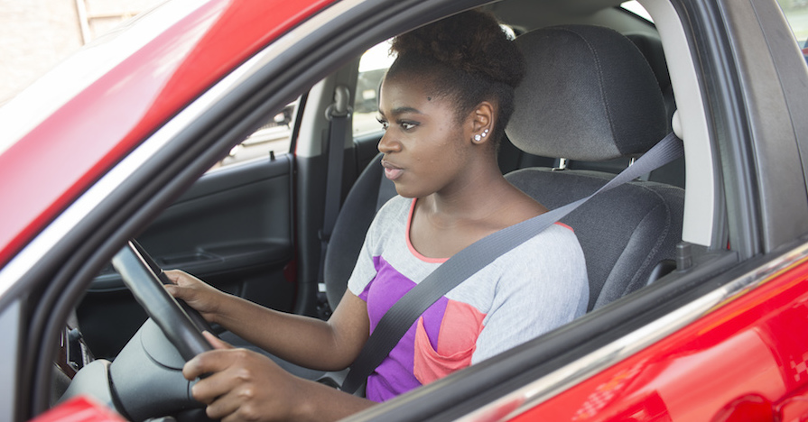 A teenage driver with both hands on the wheel, looking attentively at the road ahead.