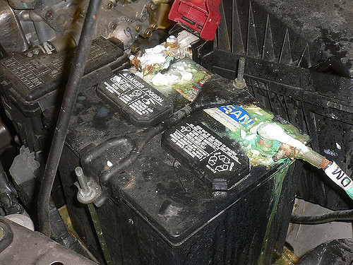 a car battery with corroded terminal ends