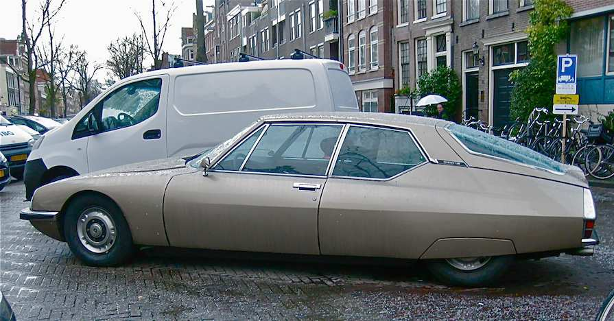 A 1973 Citroën SM classic car parked on a city street in the rain.
