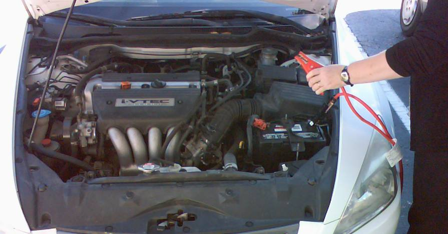 A dead car battery under the hood of a vehicle.