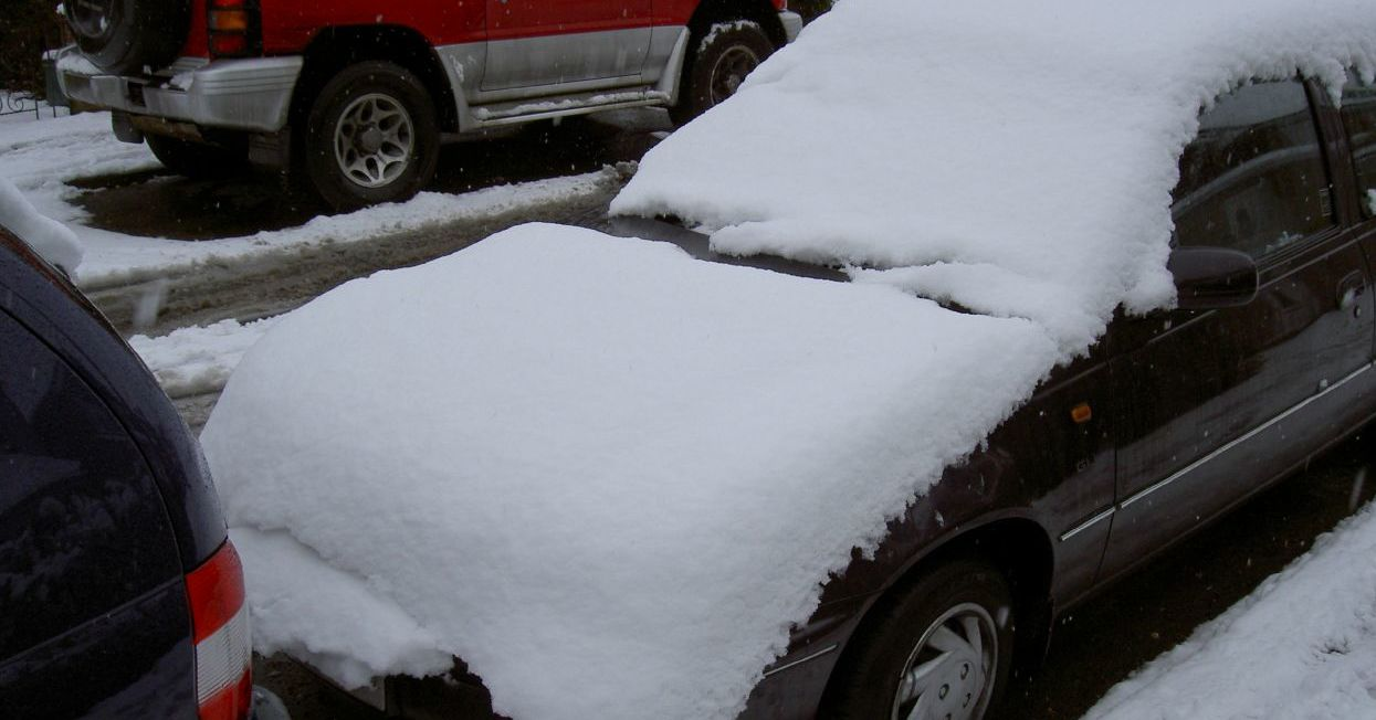 A car piled with snow that likely has a frozen fuel line.