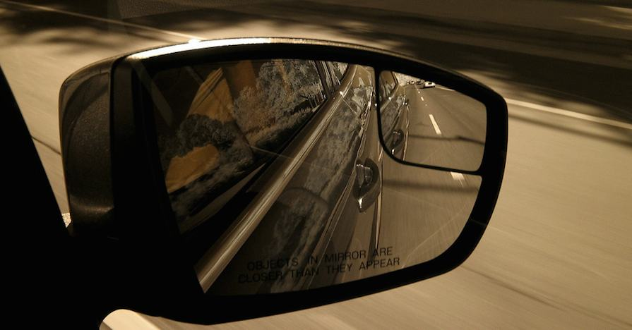 A car's side mirror with a blind-spot monitoring system.