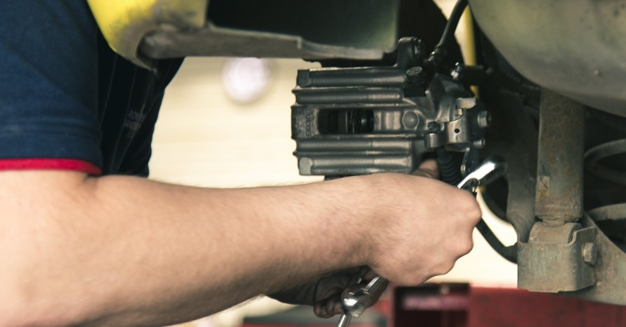A mechanic's arm adjusting an automotive component with a wrench.