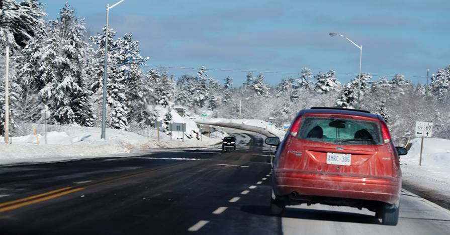 An overheating car is pulled over on side of the road on a winter day.