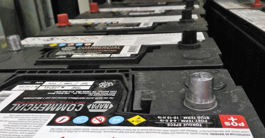 A row of car batteries displayed in an auto shop.