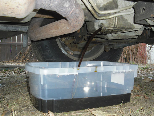 Oil being drained from a GMC Sport Utility Vehicle.