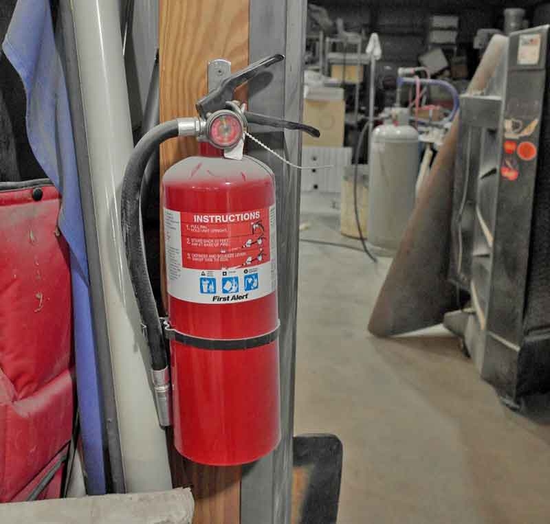 I keep an ABC extinguisher at every point of entry to the shop, as well as near the workbenches. You want a fire extinguisher within a few feet so you can catch the flames before it gets out of control.