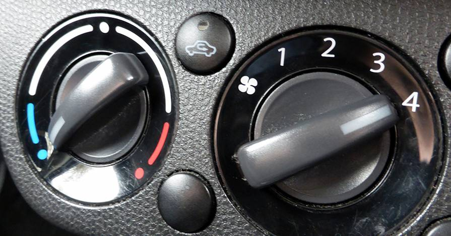 The climate control knobs on a car dashboard.