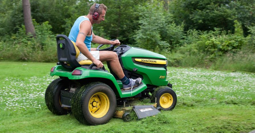 A man perched on a riding lawn mower mows his lawn.