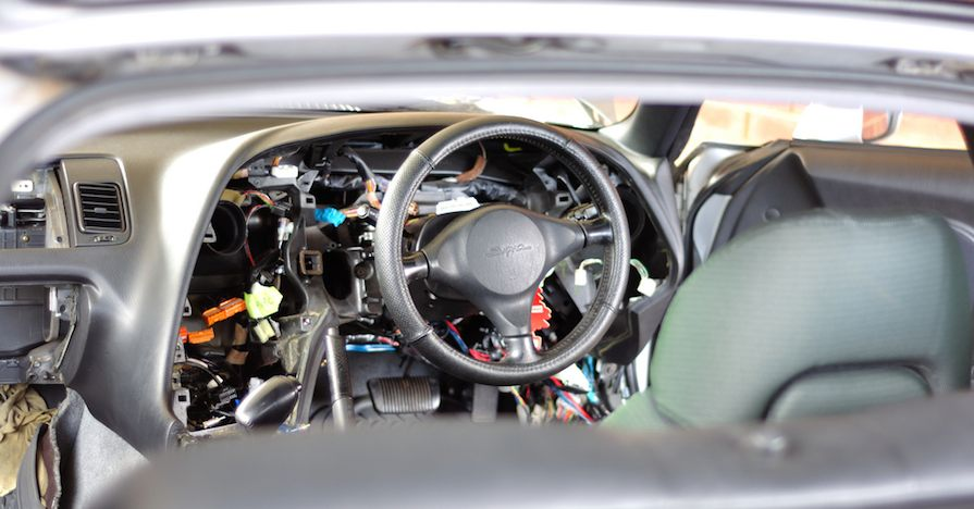 The dashboard casing has been removed from this vehicle cabin to expose a bad heater core and a tangle of other automotive components around the steering wheel.
