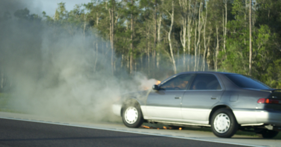 An overheating car is pulled over on the roadside, steam emanating from under the hood.