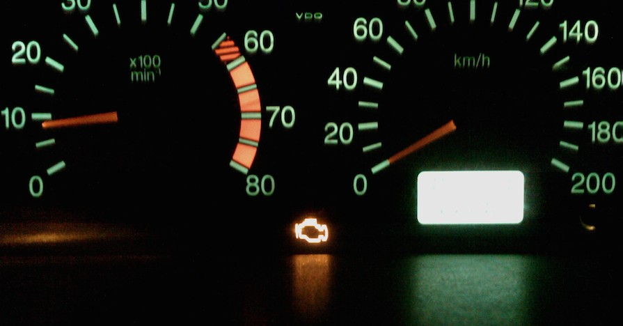 The check engine light on a dashboard is illuminated.
