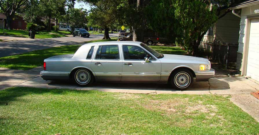 A Lincoln luxury car is parked in a driveway; its failing air suspension sags underneath it.