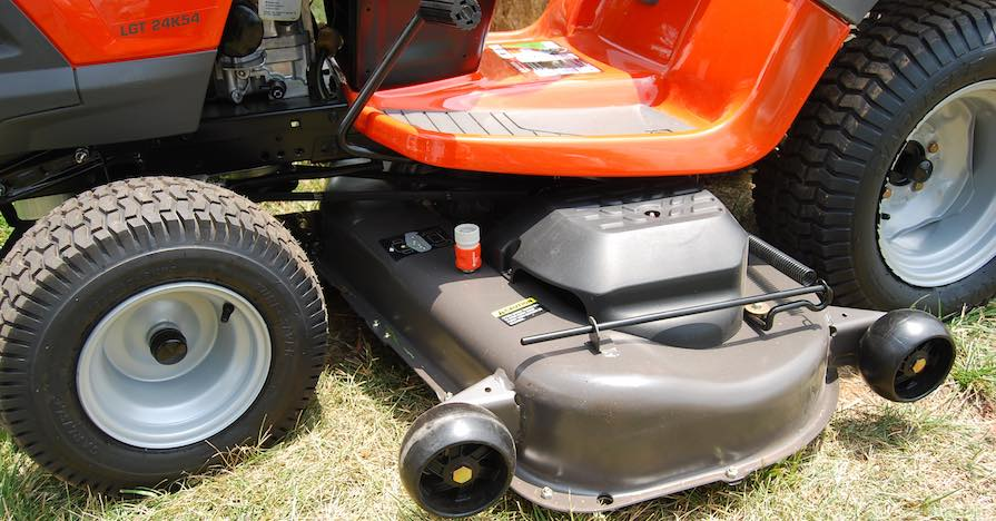 A riding lawn mower is parked on grass, with new lawn mower tires.