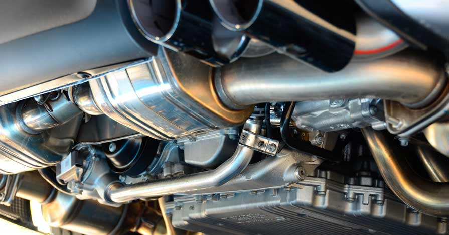 The undercarriage of a car shows an exhaust system with resonators, mufflers and exhaust tips.