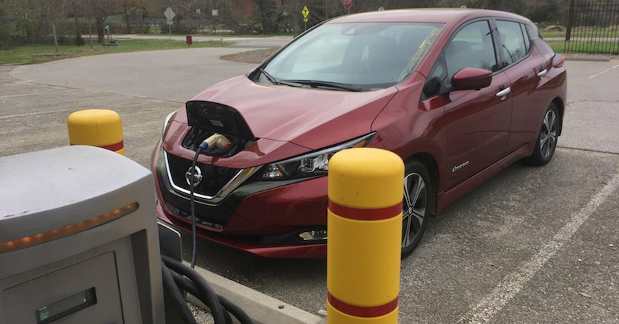 A Nissan Leaf, which is a fully electric vehicle, is connected to a charging station.