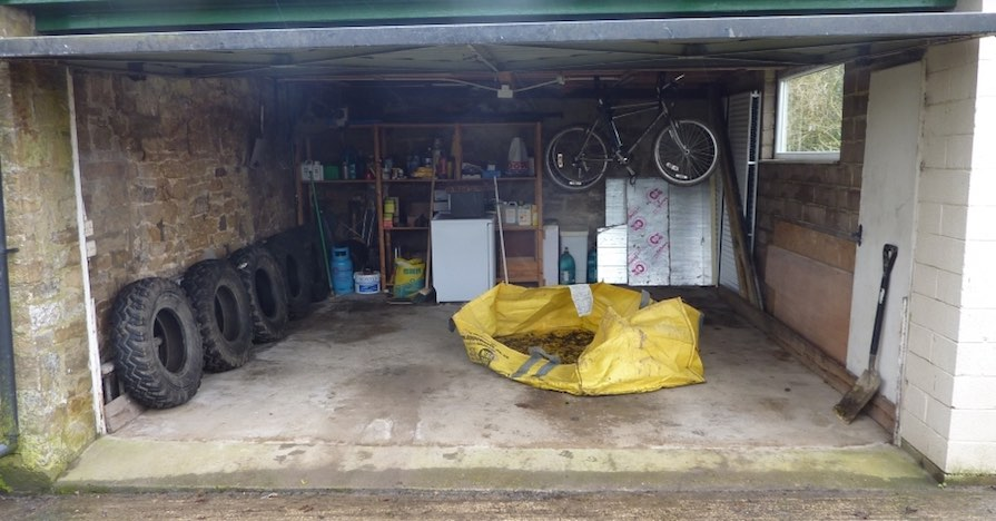 This modest, but tidy and well-organized garage has a row of tires on one wall, shelving units in the back, and a bicycle hanging from the ceiling.