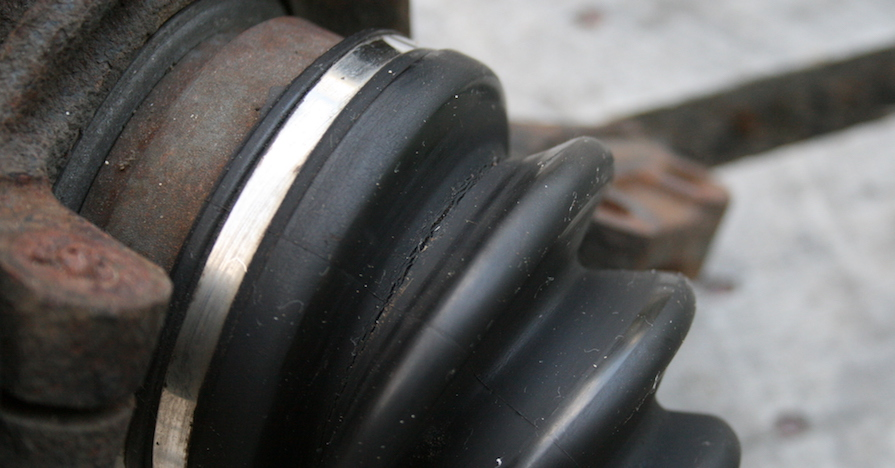 A worn constant velocity joint boot, basically a flexible rubber housing for a drivetrain axle, has a crack in the rubber.