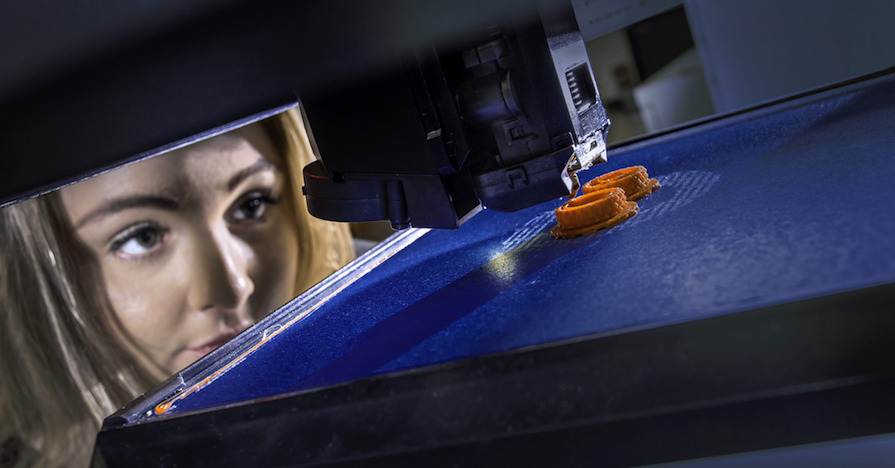 A woman watches as a 3D printer creates an object in layers.