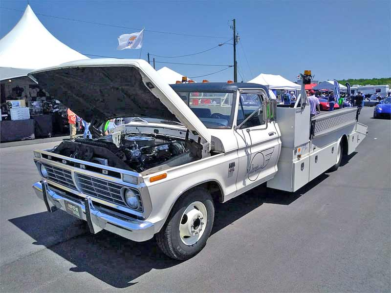A clean vintage Ford ramp truck.