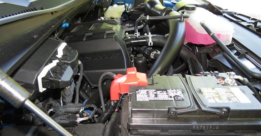 A car with a raised hood reveals the battery and alternator.