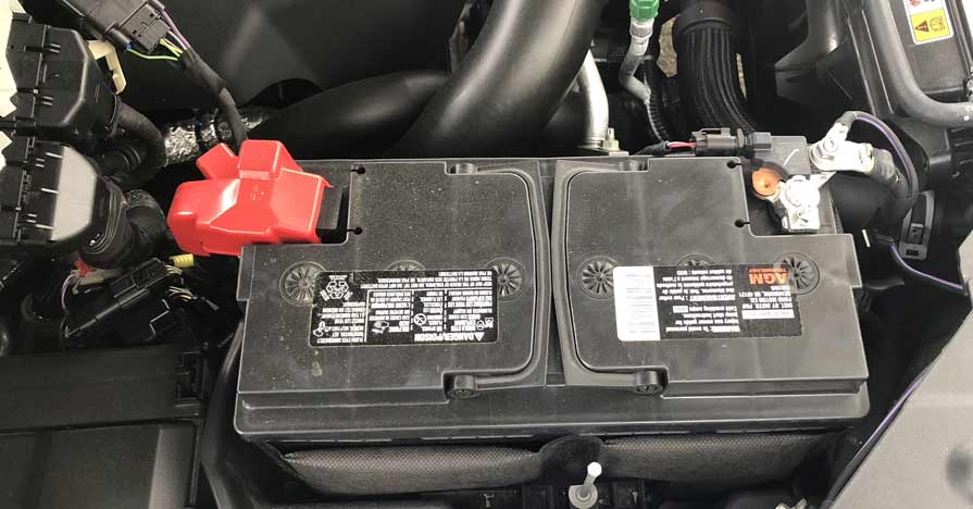 A car battery is nestled under the hood of a vehicle.