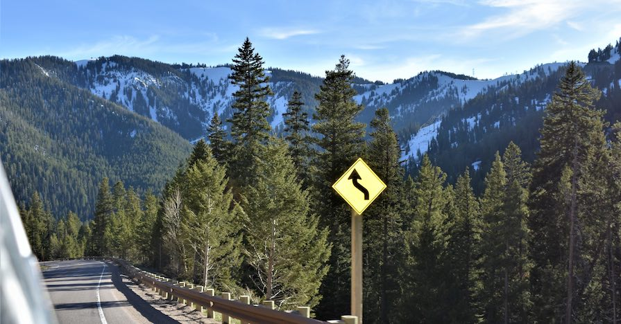 A highway bend overlooks a stand of pine trees in front of a mountain range.