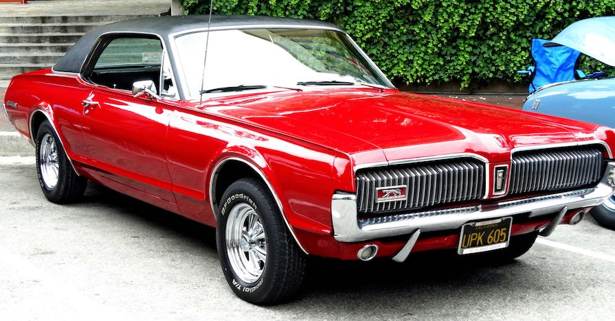 A flashy 1967 Mercury Cougar coupe at a car show.