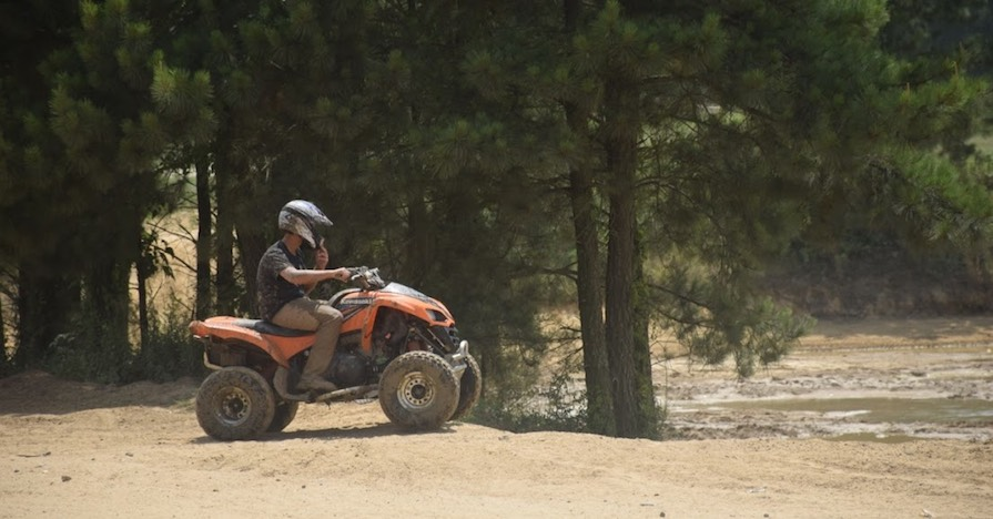 A man rides an ATV on a pine-spotted trail, with proper ATV safety gear.