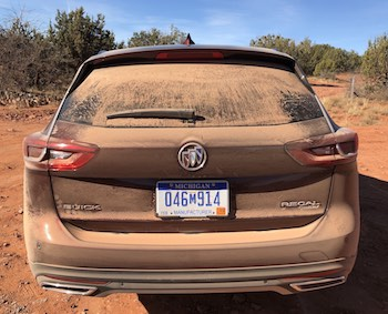 A sand-covered car in need of a good wash.