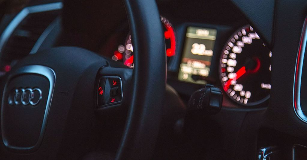 The steering wheel of a car glows in the dashboard lights.