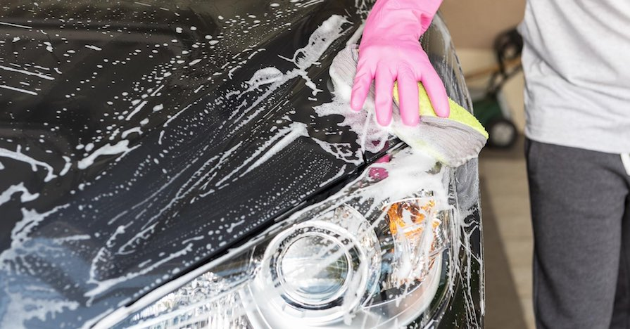 A person is washing the exterior of a car with a microfiber towel and gloves, important car cleaning products.