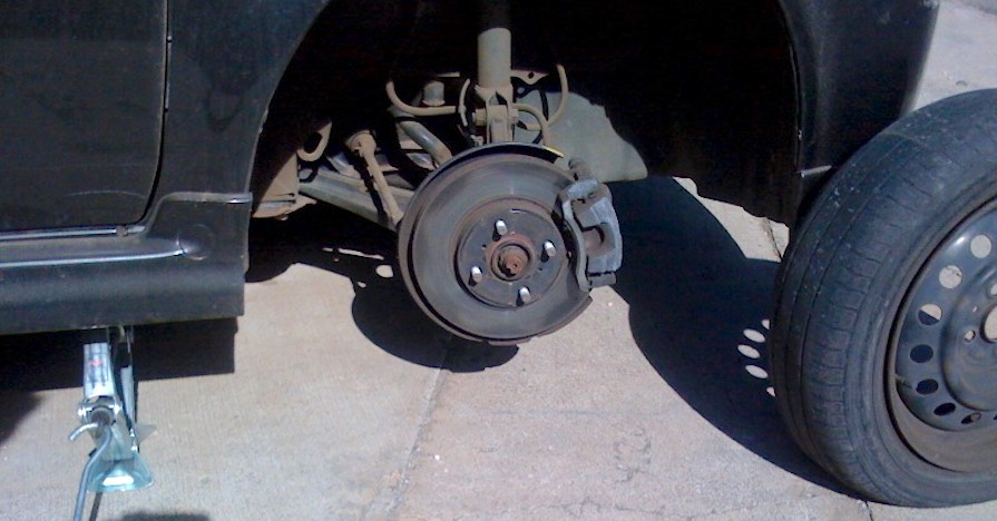 A sedan is raised with a jack, the tire removed. Jacking safely is part of learning how to change a tire.