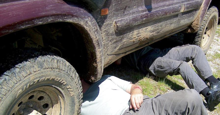 Two men with their torsos underneath a muddy SUV search for signs of common problems with differentials.