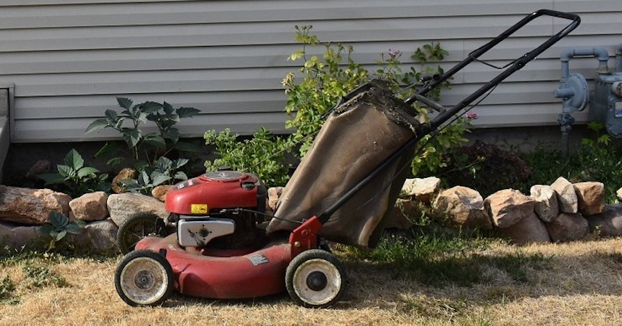 A lawn mower is parked outside a house on a small patch of grass.