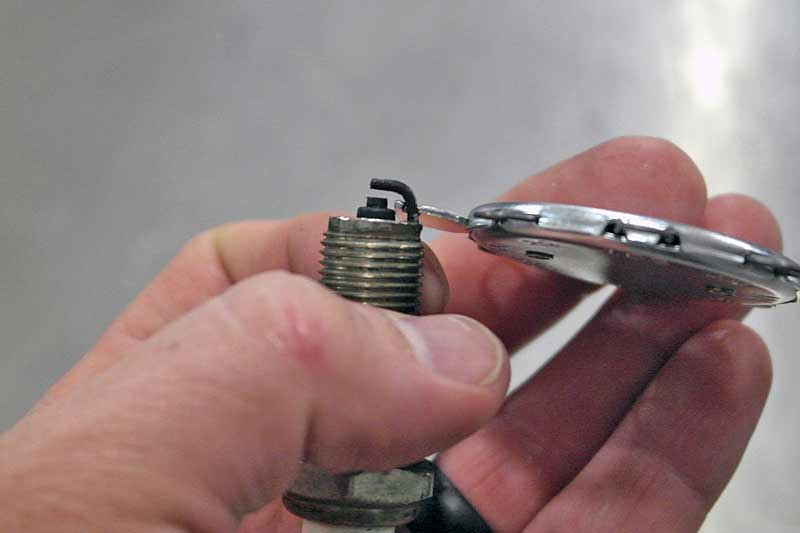 The hook on the tool is for gapping the plug. Simply pry up gently until you have reached the specified gap.