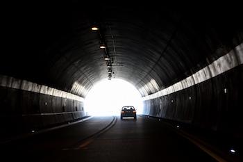 A car drives through a dark tunnel